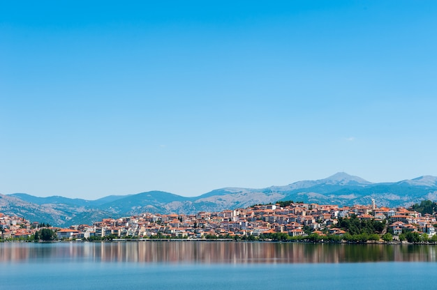 Cidade com telhados laranja perto da água e montanhas