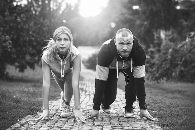 Cidade correndo casal correndo lá fora. corredores treinando ao ar livre fazendo exercícios.