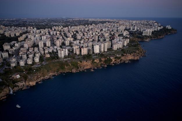 Cidade costeira mediterrânea, vista do drone. vista panorâmica da arquitetura da cidade e do mar ao pôr do sol. bela vista da paisagem urbana.