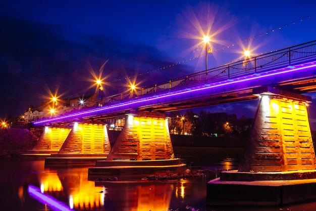 Cidade da ponte à noite refletida na água com luzes e reflexos. uzghorod uzhhorod