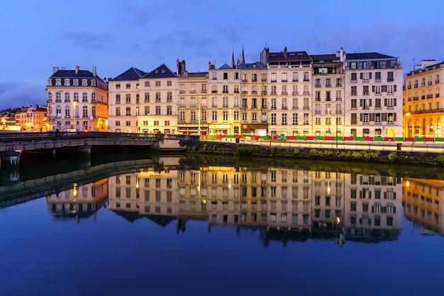Cidade de bayonne na frança à noite com casas de arquitetura típica e reflexos no rio adur. europa.