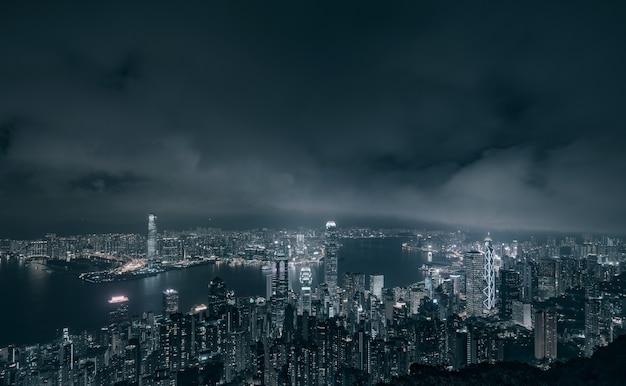 Cidade de hong kong com o porto de victoria e edifícios à noite em preto e branco