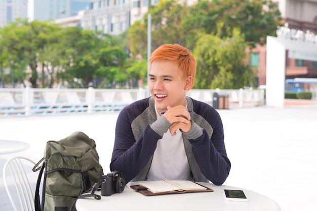 Cidade de jovem elegante em um café na cidade escrevendo notas no livro de diário
