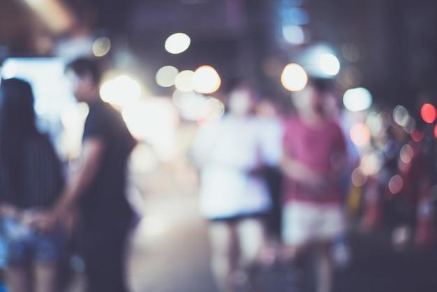 Cidade de noite desfocado lifewith carros, pessoas e lâmpadas de rua, estilo retro