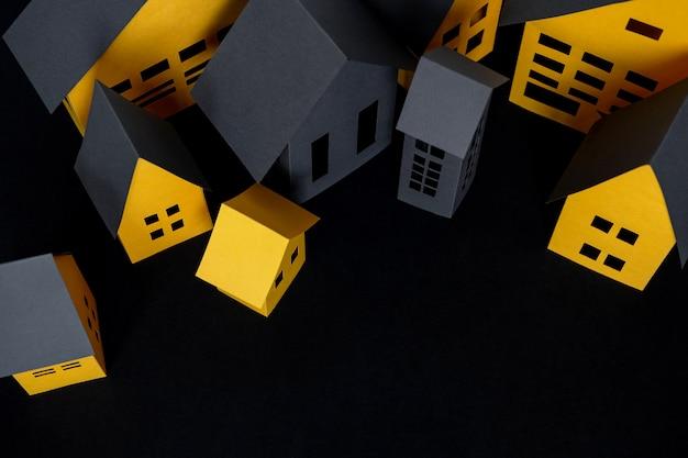 Cidade de papel cortada de um papel amarelo em fundo escuro