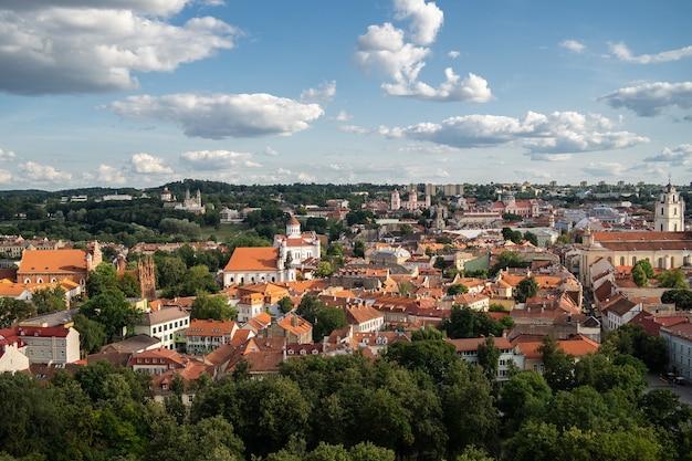 Cidade de vilnius cercada por edifícios e vegetação sob a luz do sol e um céu nublado na lituânia
