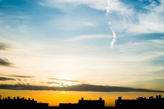 Cidade do edifício da silhueta na paisagem urbana moderna na luz solar.
