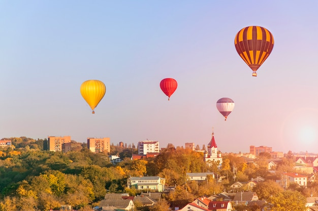 Cidade incrível - balões de ar quente coloridos voa por do sol brilhante