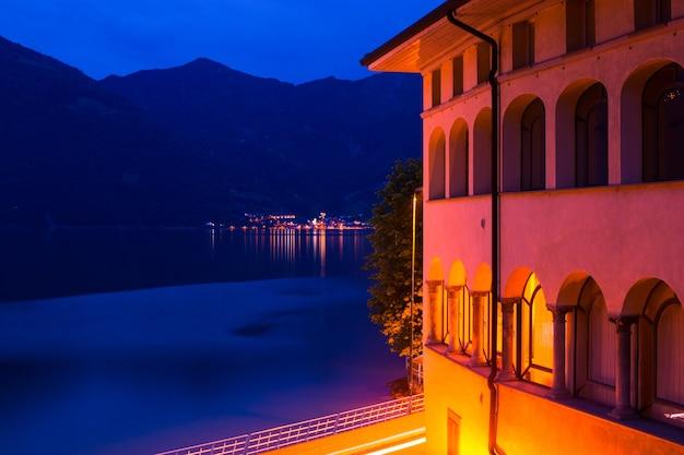 Cidade italiana noturna: um prédio com arcos iluminados e vista para o lago.