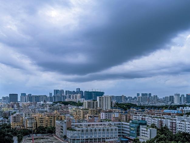 Cidade moderna e um céu cheio de nuvens escuras