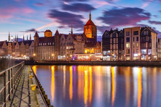 Cidade velha de gdansk, dlugie pobrzeze, bazylika mariacka ou igreja de santa maria, prefeitura e rio motlawa ao pôr do sol