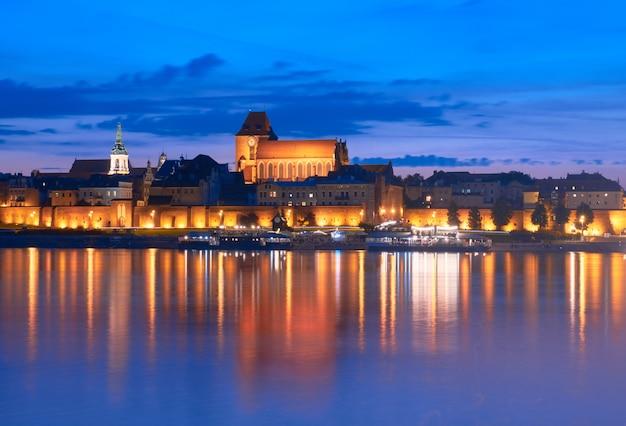 Cidade velha de torun no polônia, local do patrimônio mundial do unesco, com iluminação, refletida no rio vistula na noite bonita.