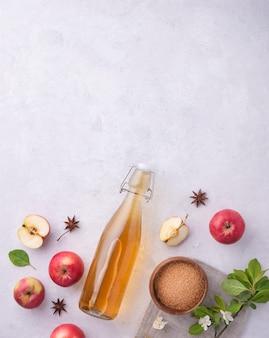 Cidra de maçã caseira fresca com especiarias em fundo cinza