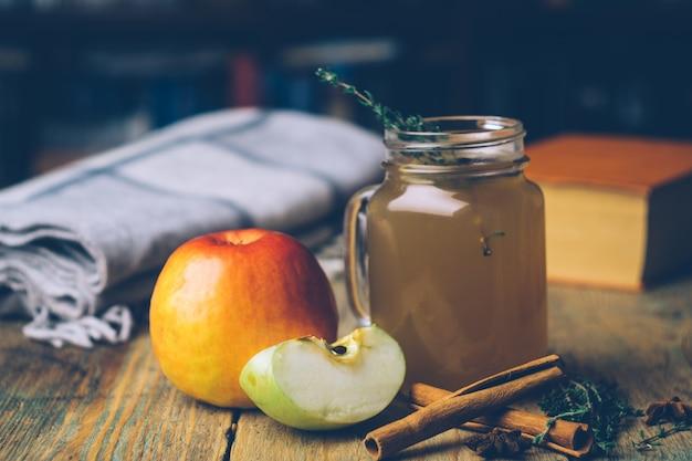 Cidra de maçã (cidra quente) com paus de canela e maçãs frescas em fundo de madeira