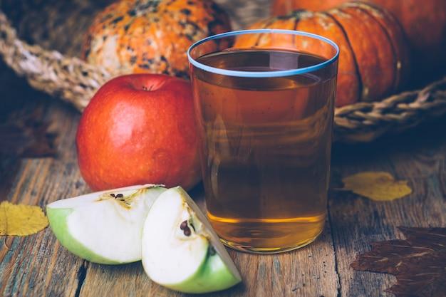 Cidra de maçã ou suco de maçã com maçãs frescas em um fundo de madeira