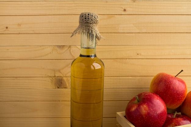 Cidra de vinagre de maçã na garrafa de vidro na madeira