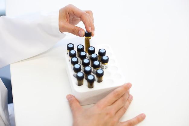 Científica manipulando tubos de ensaio de cristal em laboratório