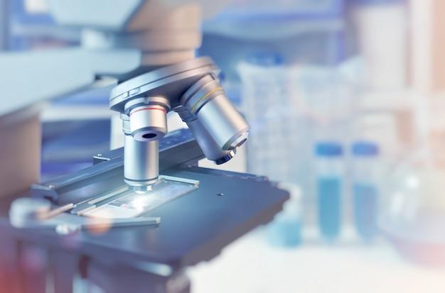 Científico com closeup no microscópio de luz e laboratório turva