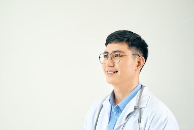 Cientista adulto ou médico vestindo jaleco branco sobre uma parede isolada, olhando para o lado com um sorriso no rosto