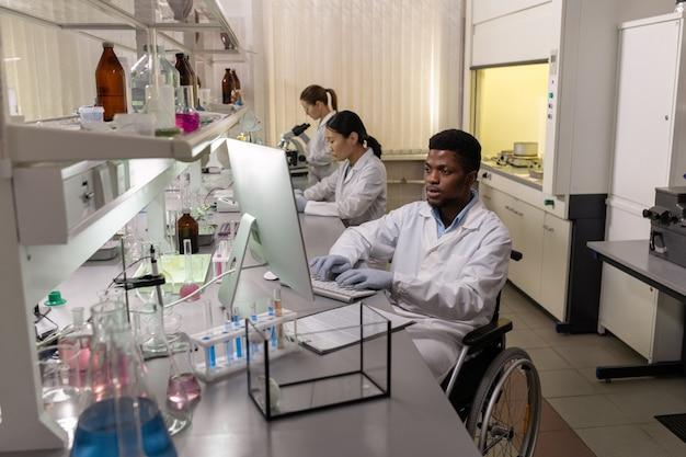 Cientista africano com deficiência sentado em uma cadeira de rodas à mesa e trabalhando no computador com seu colega no laboratório