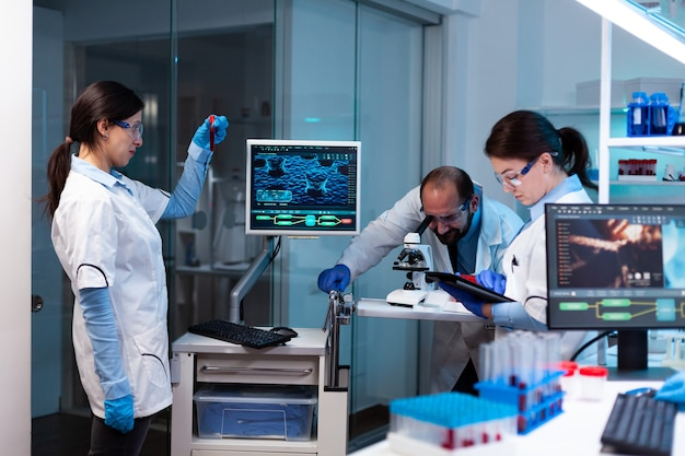 Cientista analisando amostra de sangue no vacutainer com equipe de pesquisa olhando através do microscópio Foto gratuita