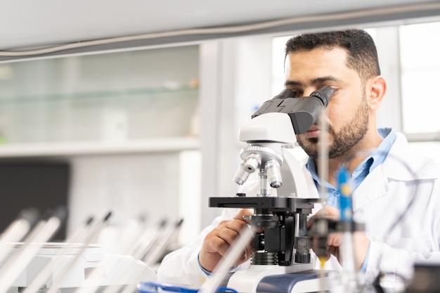 Cientista árabe usando microscópio
