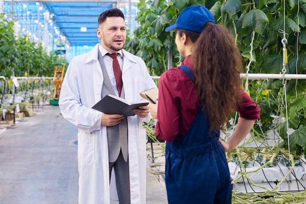 Cientista bonito falando com trabalhadora