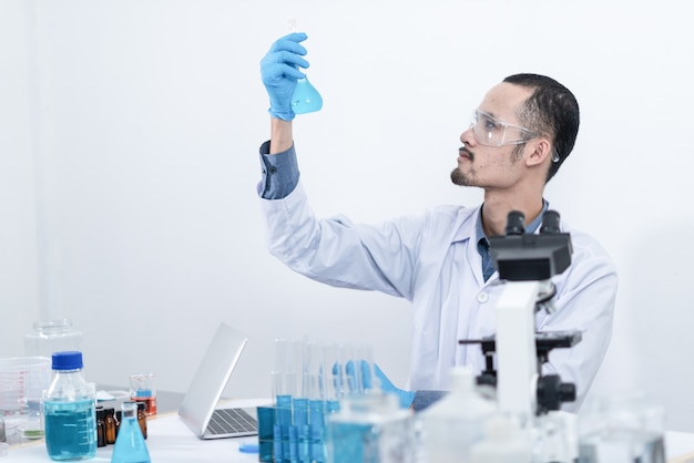 Cientista com equipamentos e experimentos científicos, vidraria contendo líquido químico para pesquisa ou análise de uma amostra em tubo de ensaio em laboratório.
