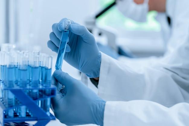 Cientista com roupas de proteção pega um tubo para teste