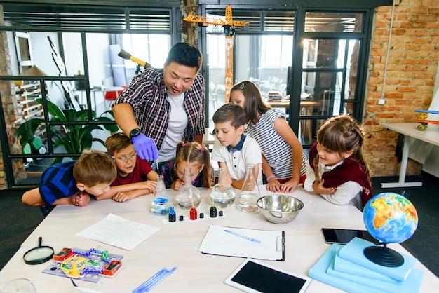 Cientista coreano mostra aos alunos da escola primária experiências de reação química na moderna aula de laboratório.