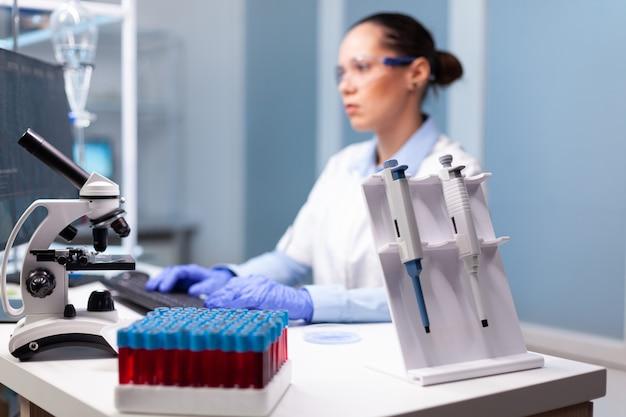Cientista da microbiologia digitando experimento de descoberta de bioquímica no computador