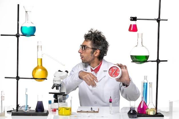Cientista de frente para o homem com roupa médica segurando relógios vermelhos na luz de fundo branco. química, vírus do laboratório secreto, saúde
