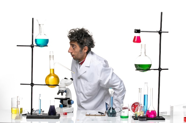 Cientista de frente para o homem em traje médico branco na frente da mesa com soluções