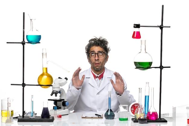Cientista de frente para o homem em traje médico branco, sentado em frente à mesa com soluções