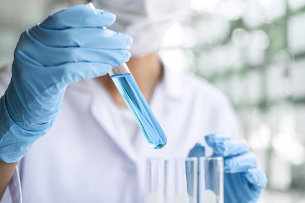 Cientista de jaleco segurando o tubo de ensaio com reagente