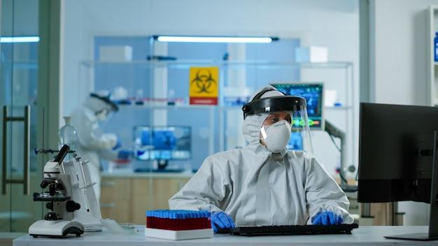 Cientista de macacão examinando tubos de teste de sangue em laboratório de análise de teste de dna, escrevendo no pc. médico que trabalha com várias bactérias, tecidos, pesquisa farmacêutica de antibióticos contra covid19