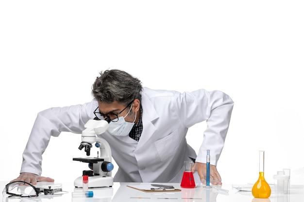 Cientista de meia-idade com visão frontal em um terno branco especial usando microscópio