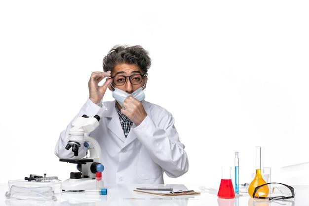 Cientista de meia-idade com visão frontal em um terno especial sentado ao redor da mesa com microscópio e soluções