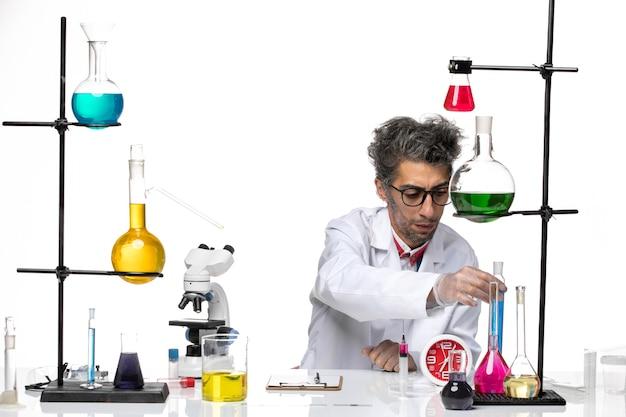 Cientista de meia-idade com vista frontal em traje médico segurando solução azul