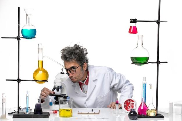 Cientista de meia-idade com vista frontal em traje médico usando microscópio
