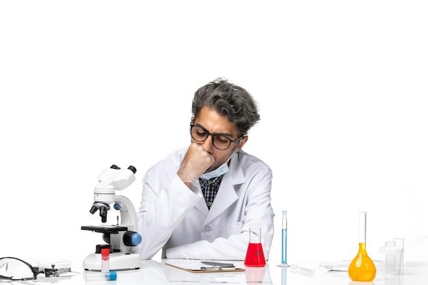 Cientista de meia-idade com vista frontal em um terno branco especial sentado ao redor da mesa com soluções