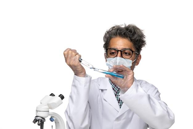 Cientista de meia-idade de vista frontal em traje médico branco preenchendo injeção com solução azul