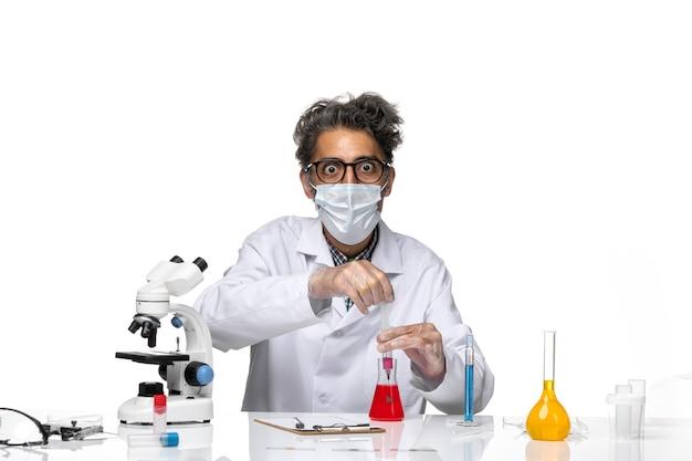 Cientista de meia-idade de vista frontal em traje médico branco preenchendo injeção com solução