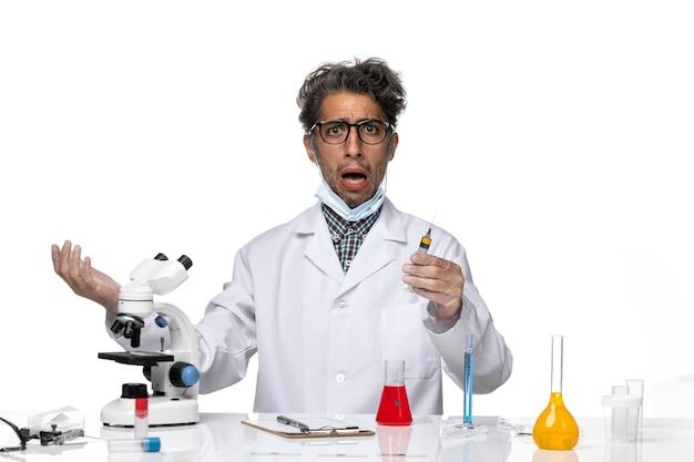 Cientista de meia-idade de vista frontal em traje médico branco preparando a injeção