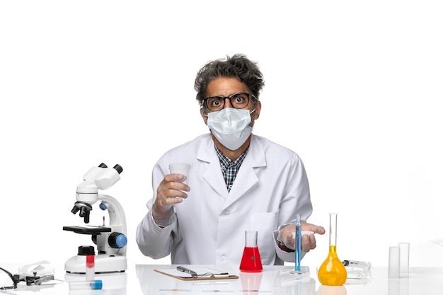 Cientista de meia-idade de vista frontal em traje médico branco segurando um frasco
