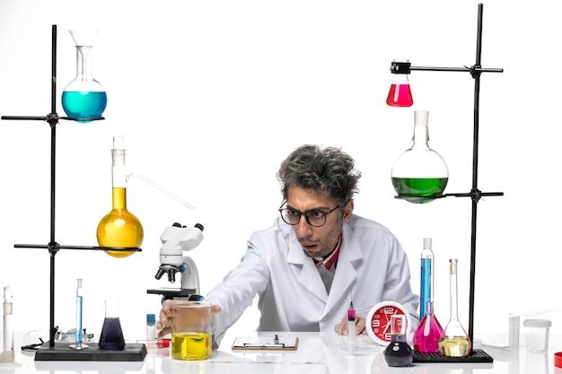 Cientista de meia-idade de vista frontal em traje médico branco sentado em frente à mesa com soluções