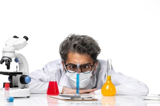 Cientista de meia-idade em um terno especial, de frente para perto, sentado com soluções e olhando para elas na mesa branca.