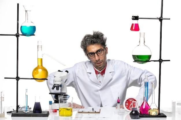 Cientista de meia-idade em vista frontal em um terno médico sentado