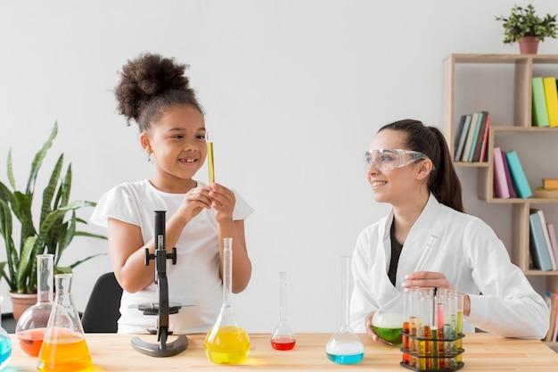 Cientista de menina e mulher tendo uma aula de ciências