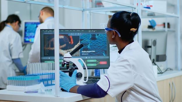 Cientista de mulher africana usando microscópio em um laboratório equipado moderno. equipe multiétnica examinando a evolução do vírus usando alta tecnologia para pesquisa científica de desenvolvimento de tratamento contra covid19.